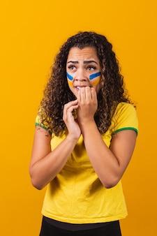 ブラジルのファンは黄色の背景でゲームに興奮し、緊張しています