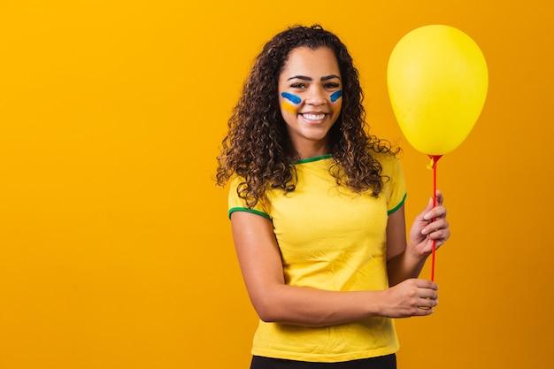Бразильский веер держит желтый воздушный шар со свободным пространством для текста. продвижение игр в бразилии