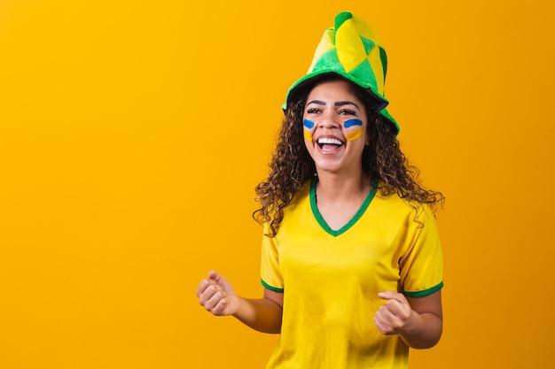 Бразильский фанат. используя краску в качестве макияжа, бразильский фанат празднует футбол или футбольный матч на желтом фоне. цвета бразилии.
