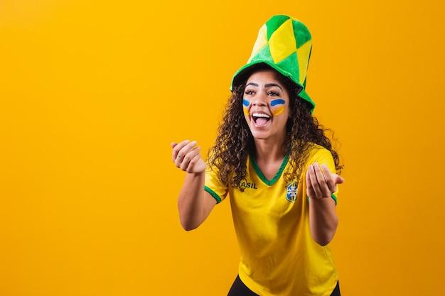 브라질 팬. 페인트를 메이크업으로 사용하는 브라질 팬은 노란색 배경에서 축구나 축구 경기를 축하합니다. 브라질의 색상입니다.