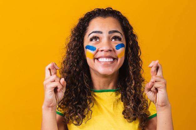 노란색 배경에 행운을 진동하는 교차 손가락을 가진 브라질 팬