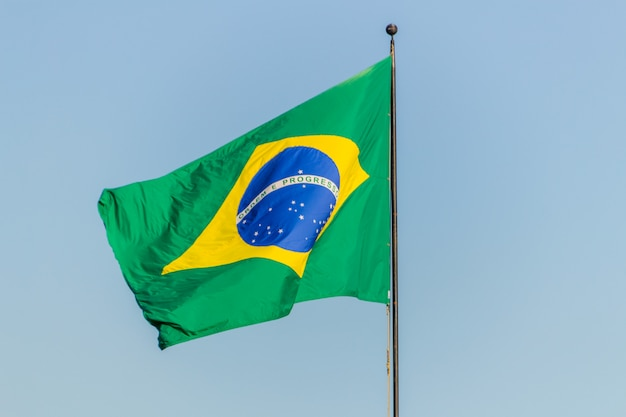 Brazilian flag flying with blue sky