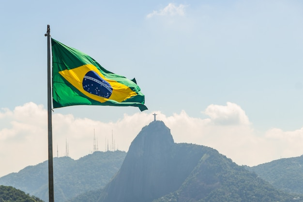 Brazilian flag with the image of the redeemer christ in the background in rio de janeiro, brazil