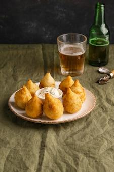 Cibo brasiliano su piastra e bicchiere di birra