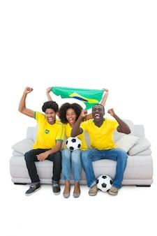 Brazilian football fans in yellow cheering on the sofa
