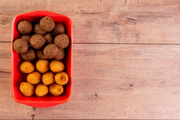 Brazilian fried savory snack mix with coxinha and fried kibbeh in red bowl