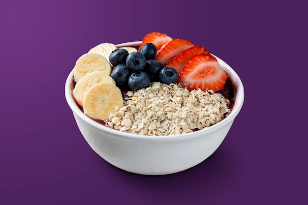 Brazilian frozen aã§ai berry ice cream bowl with strawberries, bananas, blueberry and granola. isolated on purple background. summer menu front view.