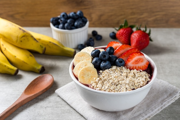 Brazilian frozen and acai berry ice cream bowl with strawberries, bananas, blueberry and oatmeal flakes. with fruits on wooden background. summer menu front view.