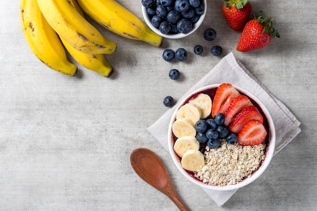 Brazilian frozen and acai berry ice cream bowl with strawberries, bananas, blueberry and oatmeal flakes. with fruits on wooden background. summer menu top view. close up