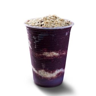 オートミールフレークのプラスチックカップにブラジルの冷凍アサイベリーアイスクリーム。白い背景で隔離。夏のメニュー正面図