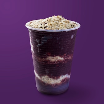 Brazilian frozen and acai berry ice cream on a plastic cup with oatmeal flakes. isolated on purple background. summer menu front view.