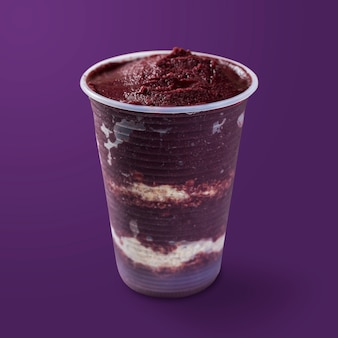 Brazilian frozen and acai berry ice cream on a plastic cup with oatmeal flakes layers. isolated on purple background. summer menu front view.