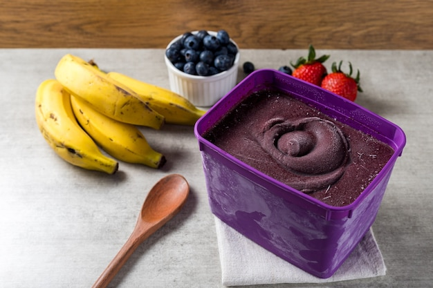 Brazilian frozen and acai berry ice cream purple pot box. with fruits on wooden background. summer menu front view.