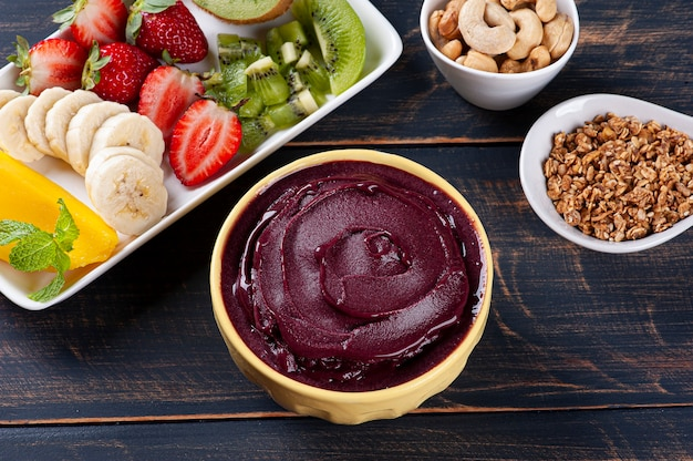 Brazilian frozen açaí­ in a bowl accompanied by tropical fruits. fruit of the amazon