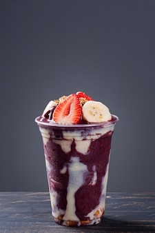 Brazilian frozen açaí­ in a plastic cup with condensed milk, banana and strawberry. fruit from the amazon.
