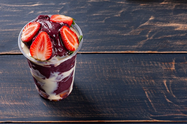 Brazilian frozen açaí­ in a plastic cup with condensed milk and strawberry. fruit from the amazon.