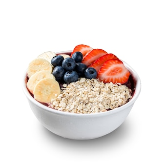 Brazilian frozen acaii berry ice cream bowl with strawberries, bananas, blueberry and granola. isolated on a white background. summer menu front view.
