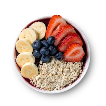 Brazilian frozen acaii berry ice cream bowl with strawberries, bananas, blueberry and oatmeal flakes. isolated on a white background. summer menu top view.