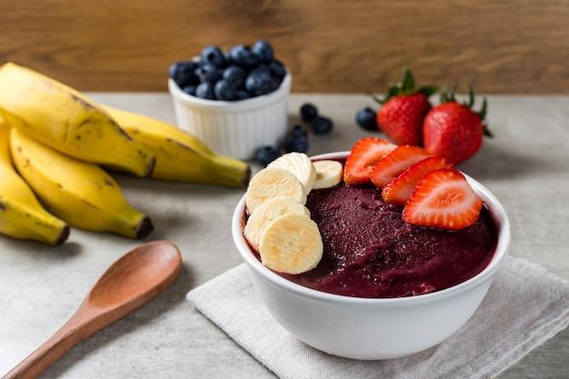 Бразильское мороженое замороженное и ягодное асаи с клубникой и бананами. с фруктами на деревянных фоне. вид спереди летнее меню.