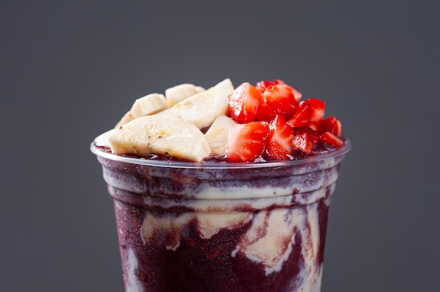 Brazilian frozen yoghurt­ in a plastic cup with condensed milk, banana and strawberry. fruit from the amazon. copy space