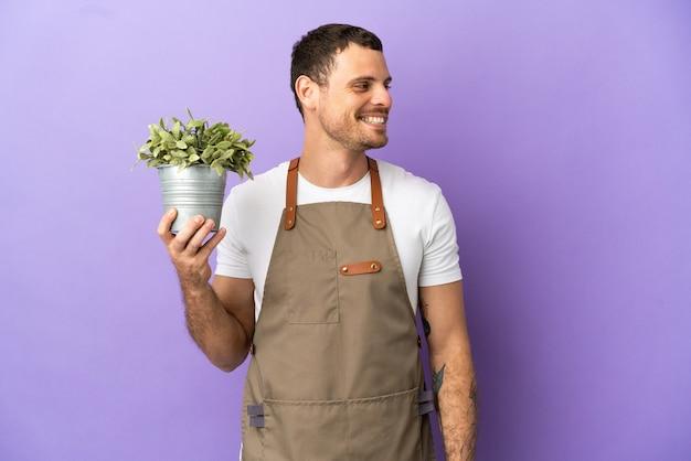 Бразильский садовник, держащий растение на изолированном фиолетовом фоне, глядя в сторону