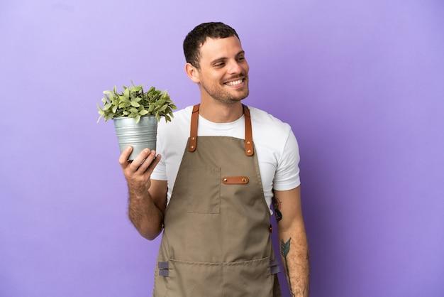 Бразильский садовник, держащий растение на изолированном фиолетовом фоне, смотрит в сторону и улыбается