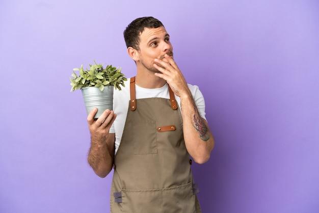 Бразильский садовник, держащий растение на изолированном фиолетовом фоне, глядя вверх, улыбаясь