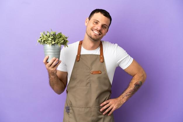 Бразильский садовник, держащий растение на изолированном фиолетовом фоне, позирует с руками на бедрах и улыбается