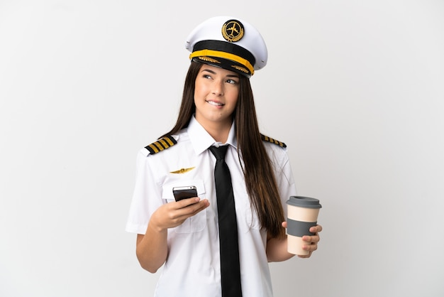 Brazilian girl airplane pilot over isolated white background holding coffee to take away and a mobile while thinking something