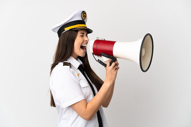 Brazilian girl airplane pilot over isolated white background shouting through a megaphone