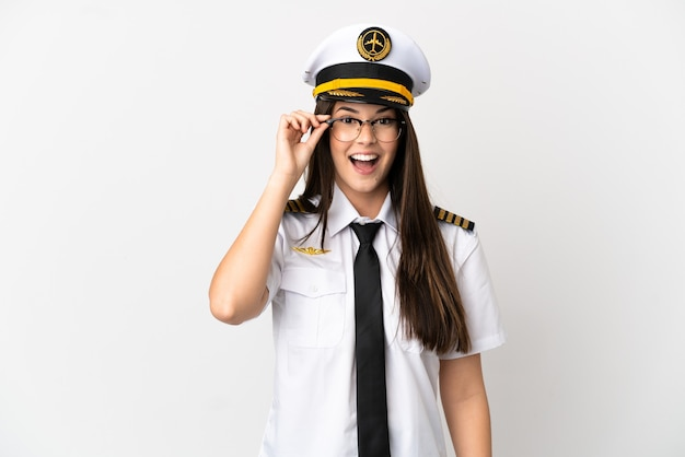 Brazilian girl airplane pilot over isolated white background with glasses and surprised