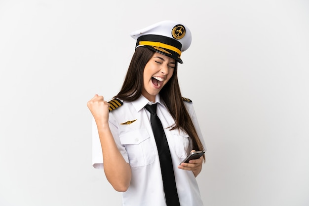 Brazilian girl airplane pilot over isolated white background with phone in victory position