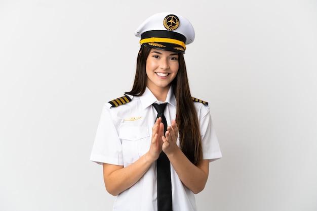 会議でのプレゼンテーションの後に拍手する孤立した白い背景の上のブラジルの女の子の飛行機のパイロット