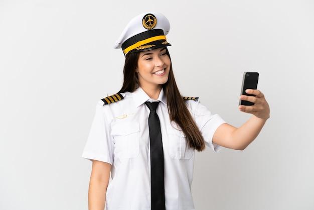 自撮りを作る孤立した白い背景の上のブラジルの女の子の飛行機のパイロット