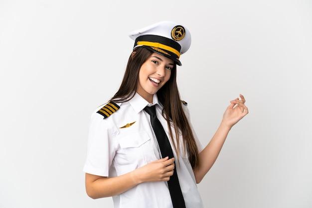 ギターのジェスチャーを作る孤立した白い背景の上のブラジルの女の子の飛行機のパイロット