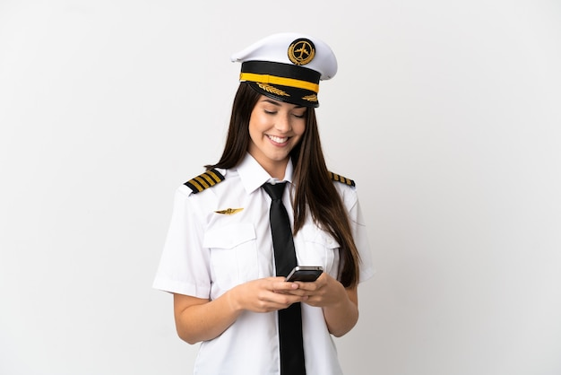Бразильская девушка пилот самолета на изолированном белом фоне, отправив сообщение с мобильного телефона