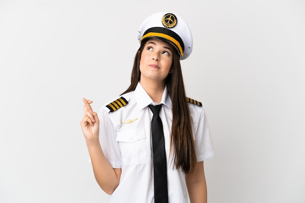 ブラジルの女の子の飛行機のパイロットは、指が交差し、最高を願って孤立した白い背景の上に