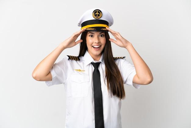 驚きの表情で孤立した白い背景の上のブラジルの女の子の飛行機のパイロット