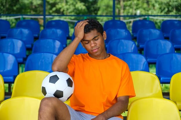 축구공을 들고 빈 축구 관람석에 앉아 있는 브라질 남자