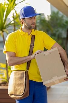 Бразильский почтальон доставляет посылку на улице. интернет-покупка доставляется на дом.