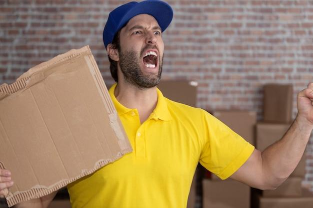 ブラジルの郵便配達員が、たくさんの箱のある預金に空白のボードを持っています。コピースペース。