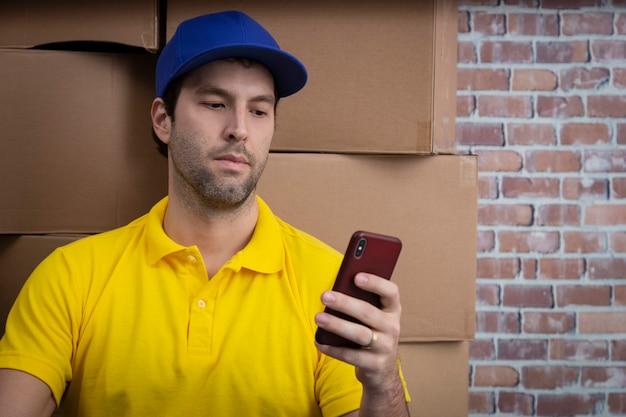 たくさんの箱が付いている預金でスマートフォンを使用しているブラジルの郵便配達員。