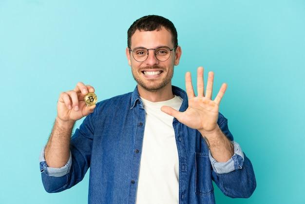Бразильский мужчина держит биткойн на синем фоне, считая пять пальцами