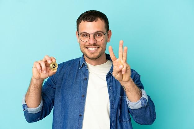 Бразильский мужчина держит биткойн на изолированном синем фоне счастлив и считает три пальцами