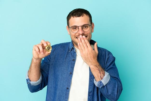 Бразильский мужчина держит биткойн на синем фоне, счастливый и улыбающийся, прикрывая рот рукой