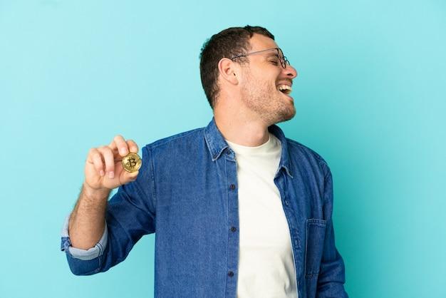 横向きの位置で笑っている孤立した青い背景の上にビットコインを保持しているブラジル人男性