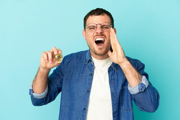 Бразильский мужчина держит биткойн на синем фоне и кричит с широко открытым ртом