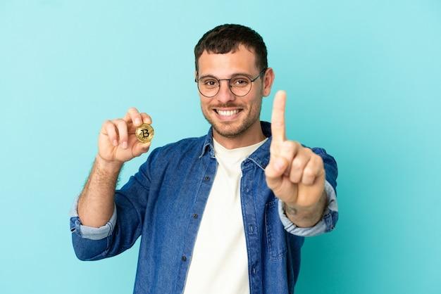 Бразильский мужчина, держащий биткойн на синем фоне, показывает и поднимает палец
