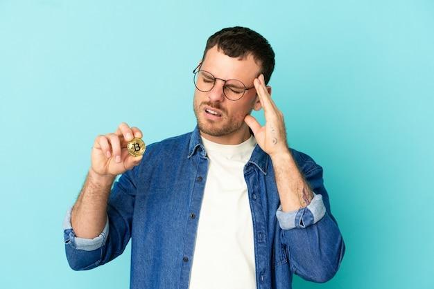 두통과 격리 된 파란색 배경 위에 bitcoin을 들고 브라질 남자