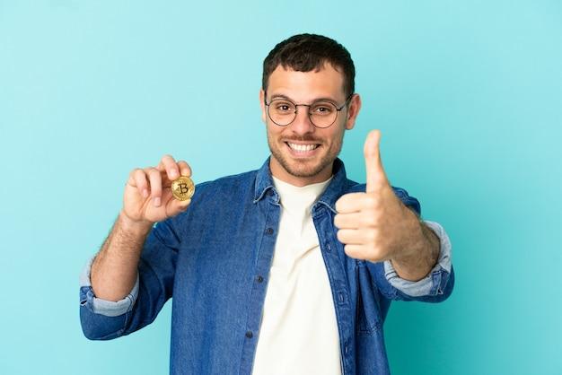 何か良いことが起こったので、親指を立てて孤立した青い背景の上にビットコインを保持しているブラジル人男性